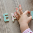 Child is Writing Word Peace From Colourful Toy Letters — Stock Photo #78894228