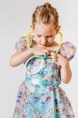 Menina brincando com seu estetoscópio de brinquedo — Fotografia Stock