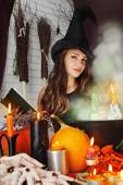 Witch near the boiler with book — Stock Photo