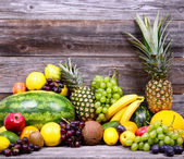 Huge group of fresh colorful fruit on wooden background - Health — Stock Photo
