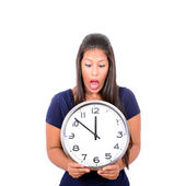 Portrait of a young female in shock holding big clock against wh — Stock Photo