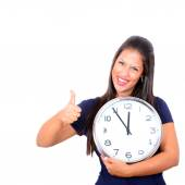 Portrait of beautiful young woman holding big clock with thumbs  — Stock Photo
