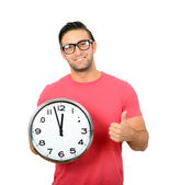 Happy young handsome man holding clock in his hand with thumb up — Stock Photo