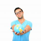 Portrait of young handsome man holding globe in hands against wh — Stock Photo