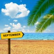 Tropical beach and direction board saying SEPTEMBER — Stock Photo #54512383