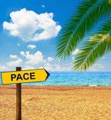 Tropical beach and direction board saying PACE — Stock Photo