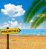 Tropical beach and direction board saying PRIORITIES — Stock Photo