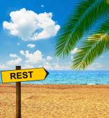 Tropical beach and direction board saying REST — Stock Photo