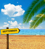 Tropical beach and direction board saying SEPTEMBER — Stock Photo