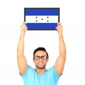 Portrait of a young casual man holding up board with National fl — Stock Photo