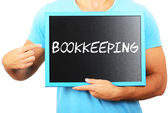 Man holding blackboard in hands and pointing the word BOOKKEEPIN — Stock Photo