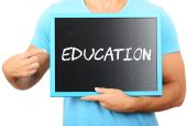 Man holding blackboard in hands and pointing the word EDUCATION — Stock Photo