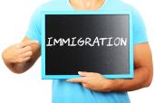 Man holding blackboard in hands and pointing the word IMMIGRATIO — Stock Photo