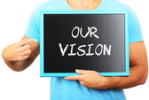 Man holding blackboard in hands and pointing the word OUR VISION — Stock Photo