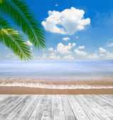 Tropical sea and beach with palm leaves and wooden floor — Stock Photo