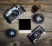 Vintage cameras with lenses and blank old photograph on wooden b — Stok fotoğraf