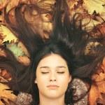 Portrait of beautiful brunette woman lying on maple leaves — Stock Photo #57222911