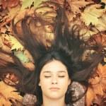 Portrait of beautiful brunette woman lying on maple leaves — Stock Photo #57223081
