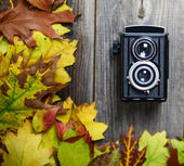 Retro camera on wooden table with autumn leaves — Stock Photo
