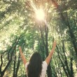 Young woman with arms raised enjoying the fresh air in green for — Stock Photo #57920455