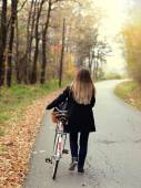 Girl riding a bike in forest — Stock Photo