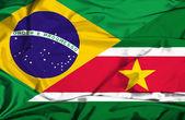Waving flag of Suriname and Brazil — Stock Photo