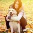 Brunette girl with dog in nature — Stock Photo #70452645