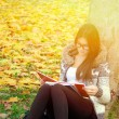 Beautiful brunette girl reading book in nature — Stock Photo #70452813