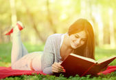 Beautiful smiling woman reading book in park — Stock Photo