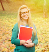 Portrait of smiling student girl holding books — Stock Photo