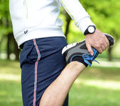 Handsome sportsman stretching outdoors — Stock Photo