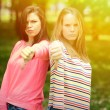 Two attractive girls show thumbs down against green nature backg — Stock Photo #72887869