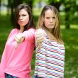 Two attractive girls show thumbs down against green nature backg — Stock Photo #72887899