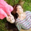 Two girl friends listening to music while lying on grass during — Stock Photo #72888017