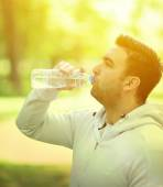 Fit young sportsman drinking water from plastic bottle after wor — Stock Photo