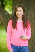 Female student girl outside in park listening to music on headph — Stockfoto