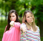 Two attractive girls show thumbs down against green nature backg — Stock Photo