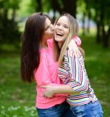 Two young girl friends in a hug at park — Stock Photo