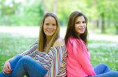 Two young girl friends sitting on grass at summer day — Stock Photo