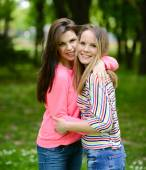 Two young girl friends together in hug at park — Stock Photo