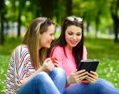 Young women drinking coffee and browsing internet on tablet at p — Stock Photo