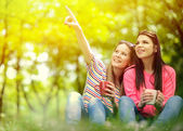 Young women drinking coffee at park and enjoying summer day — Stock Photo