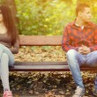 Young couple in quarrel sitting on bench in park — Stock Photo #72922483