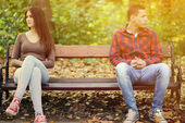 Young couple in quarrel sitting on bench in park — Stock Photo