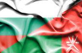 Waving flag of Oman and Bulgaria — Stock Photo