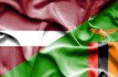Waving flag of Zimbabwe and Latvia — Stock Photo