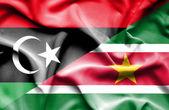Waving flag of Suriname and Libya — Stock Photo