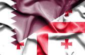 Waving flag of Georgia and Qatar — Stock Photo