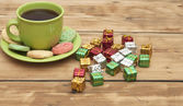 Gifts boxes with a colorful happy birthday cookie and tea cup — Stock Photo