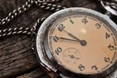 Old pocket watch on a rustic vintage wooden background — Stock Photo
